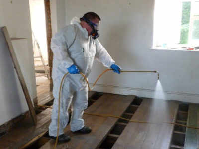Contractor using chemicals to treat timber